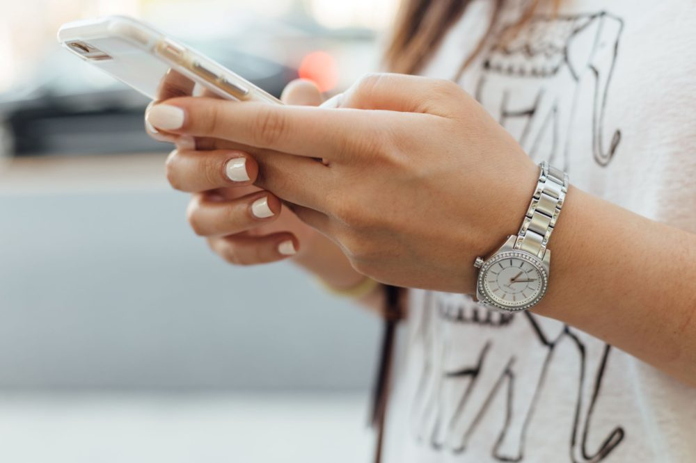woman's hands holding cell phone