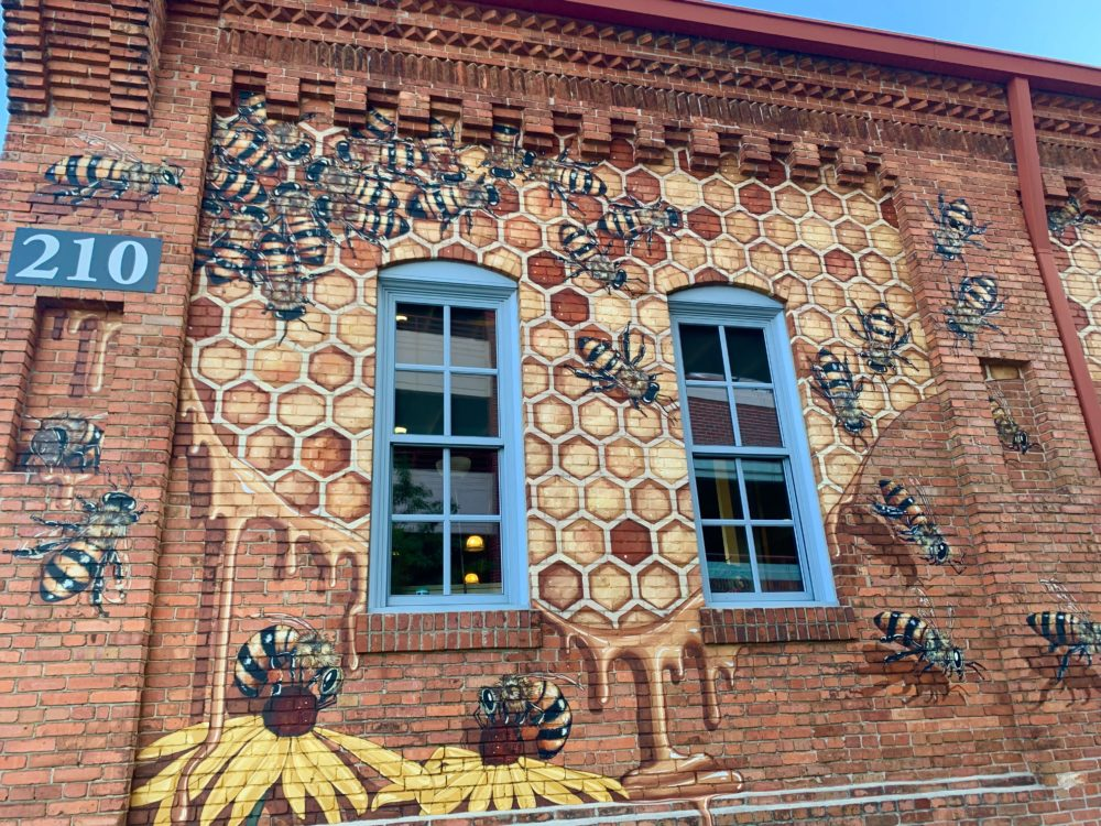 mural of honey bees in hive and on flowers on brick building outside Burt's Bees headquarters