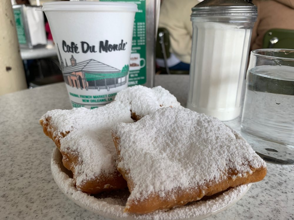 beignets (fried dough covered in powdered sugar) and coffee cup at Cafe du Monde in New Orleans