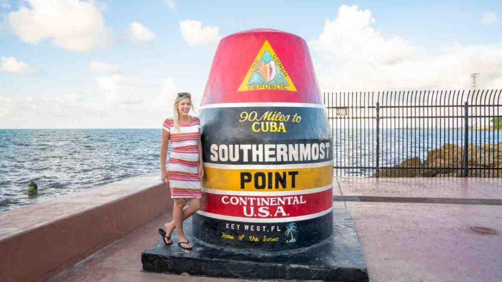 The Best Caribbean Cruise Shore Excursions to do on Port Day featured by top cruise blog, The Common Traveler: image of woman standing next to Key West Southern most point in continental USA marker