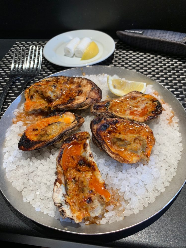 plate of broiled oysters on the half-shell on bed of rock salt