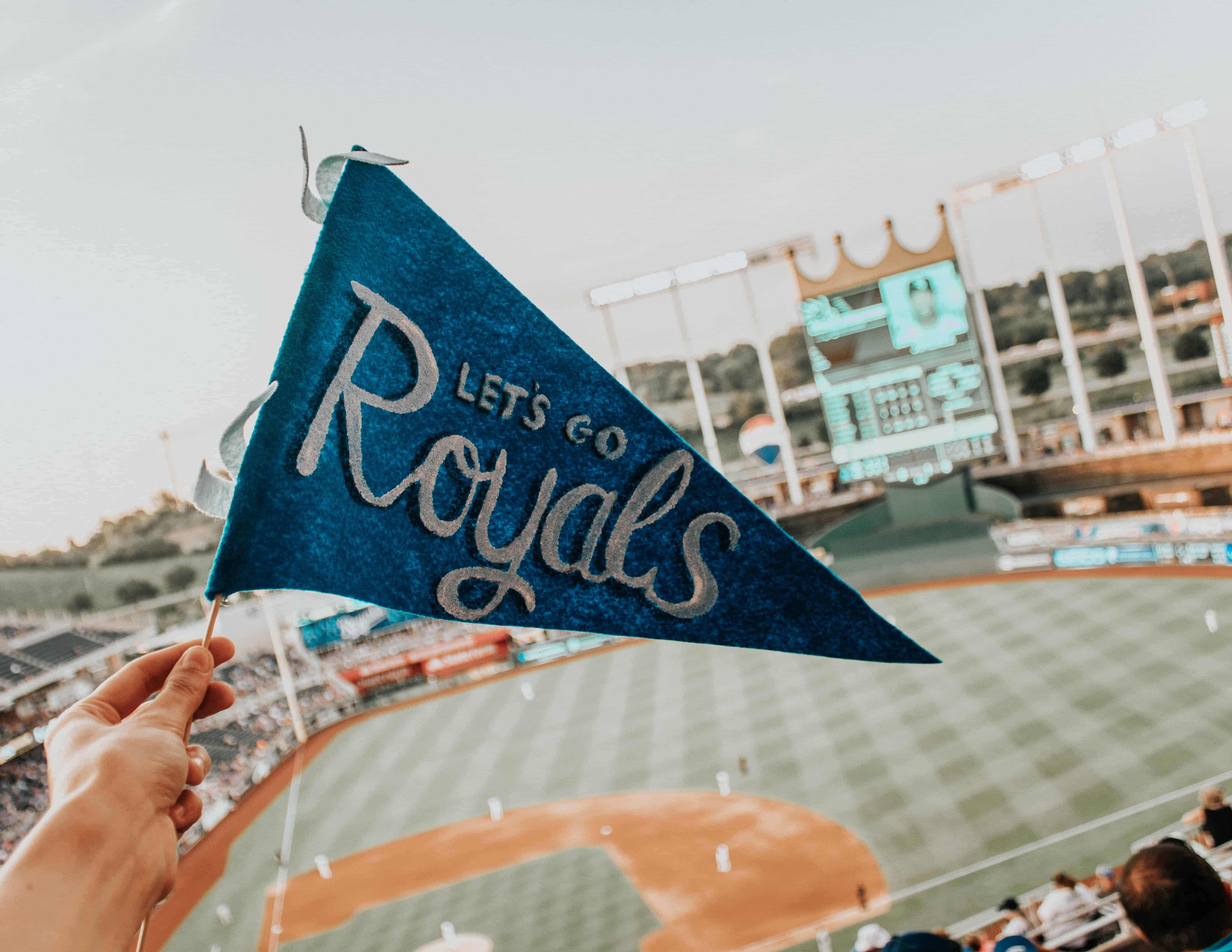 """blue penant with """"Let's Go Royals"""" in front of baseball field"""