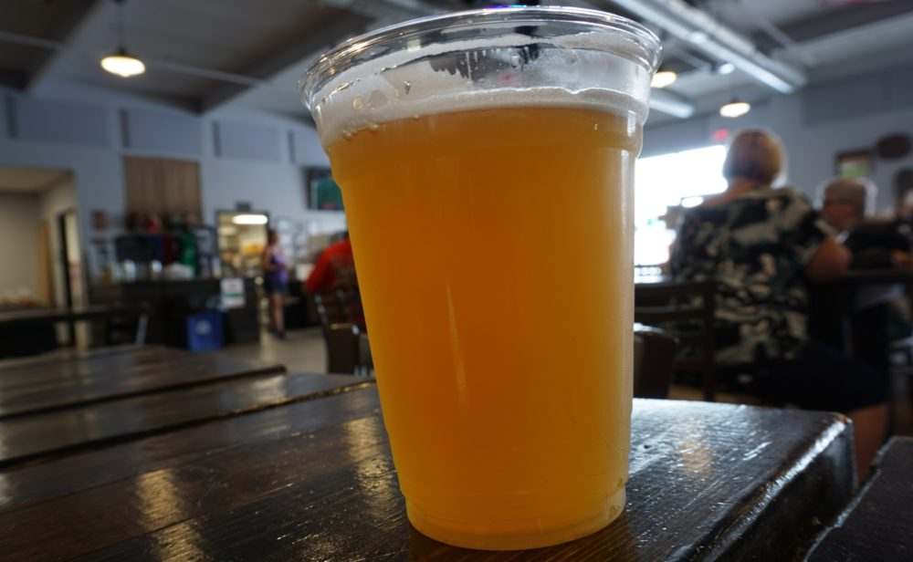 12 FUN THINGS TO DO IN OXFORD NC featured by top NC travel blog, The Common Traveler: image of pint of beer in plastic cup
