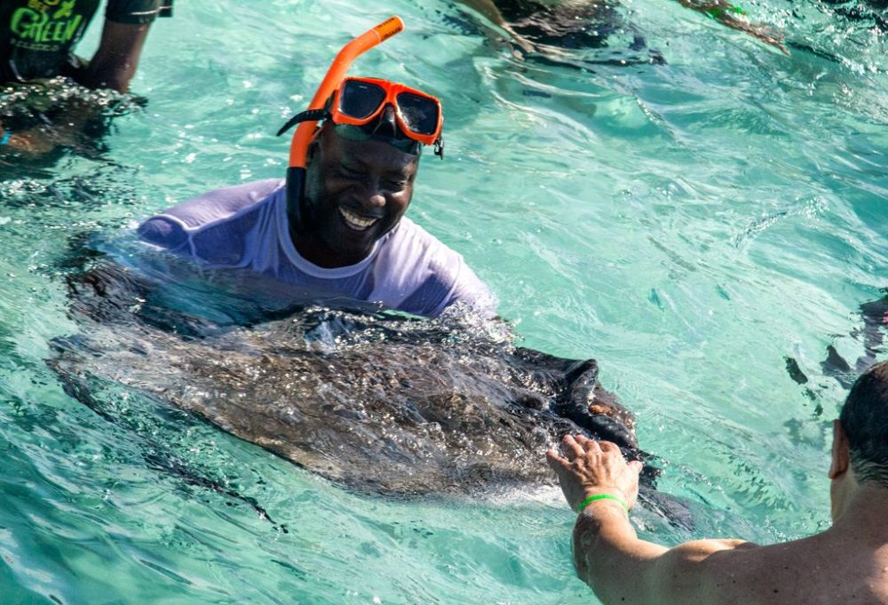 The Best Caribbean Cruise Shore Excursions to do on Port Day featured by top cruise blog, The Common Traveler: image of Smiling man holding stingray in Grand Cayman