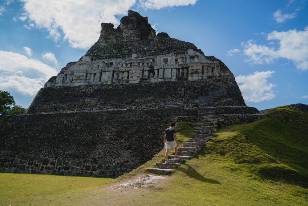Top 10 Best Things To Do in Belize featured by top US travel blog, The Common Traveler: image of Belize's Xunantunich ruins with man climbing stairs