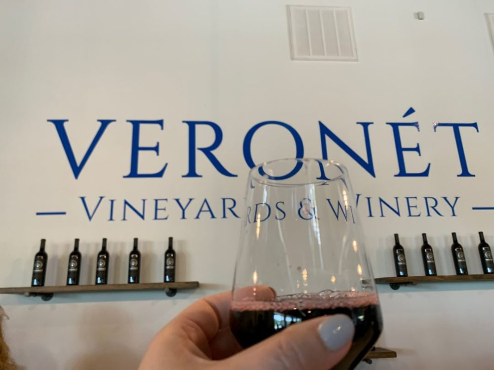 Ridgeline Craft Beverage Trail featured by top NC travel blog, The Common Traveler: Veronet Vineyards and Winery sign with glass of red wine in foreground