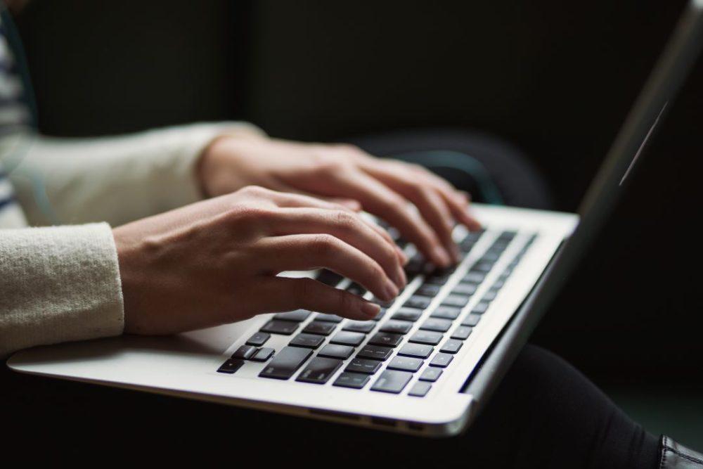 woman's fingers on laptop keyboard