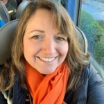 photo of woman with orange scarf on bus with black winter coat