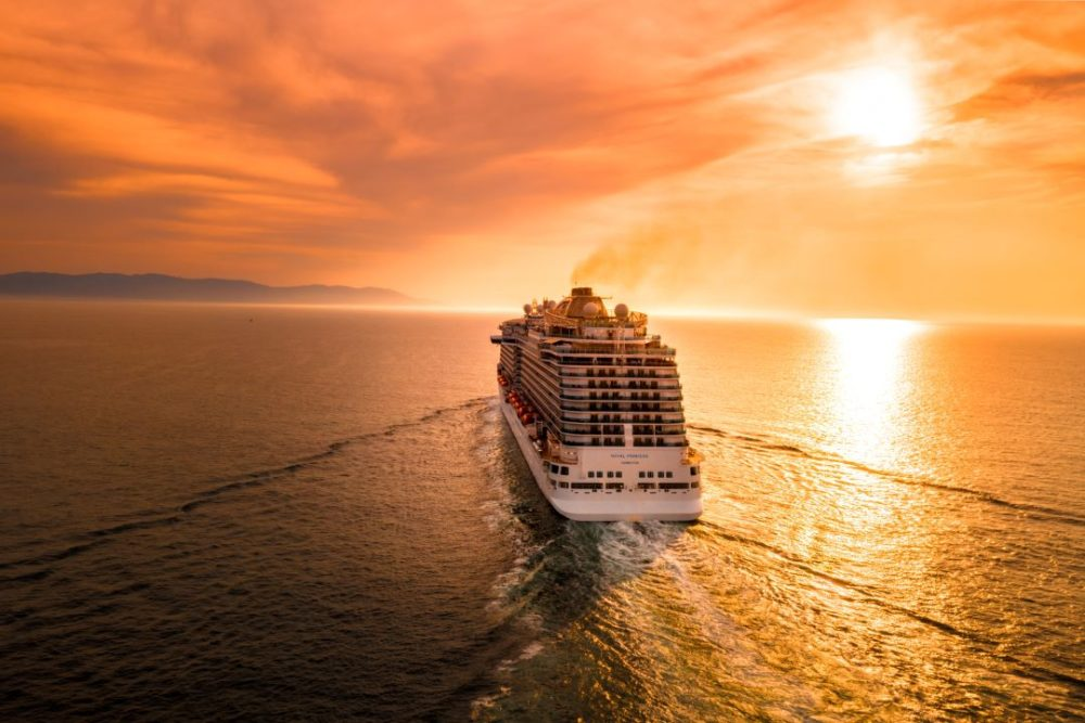 9 Essential Cruise Embarkation Tips for the First Time Cruiser featured by affordable travel blog The Common Traveler - image: cruise ship sailing into setting sun