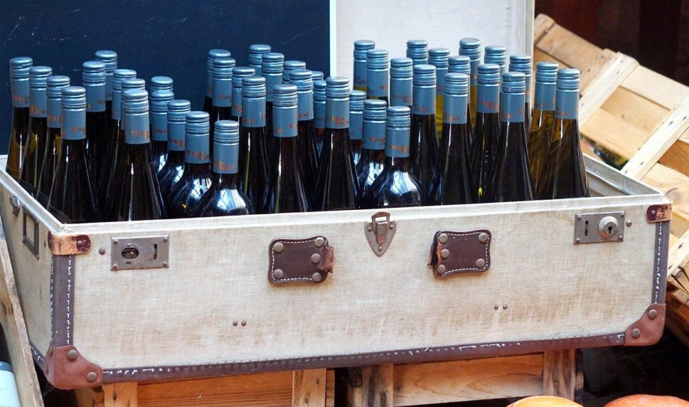 9 Essential Cruise Embarkation Tips for the First Time Cruiser featured by affordable travel blog The Common Traveler - image: suitcase full of wine bottles