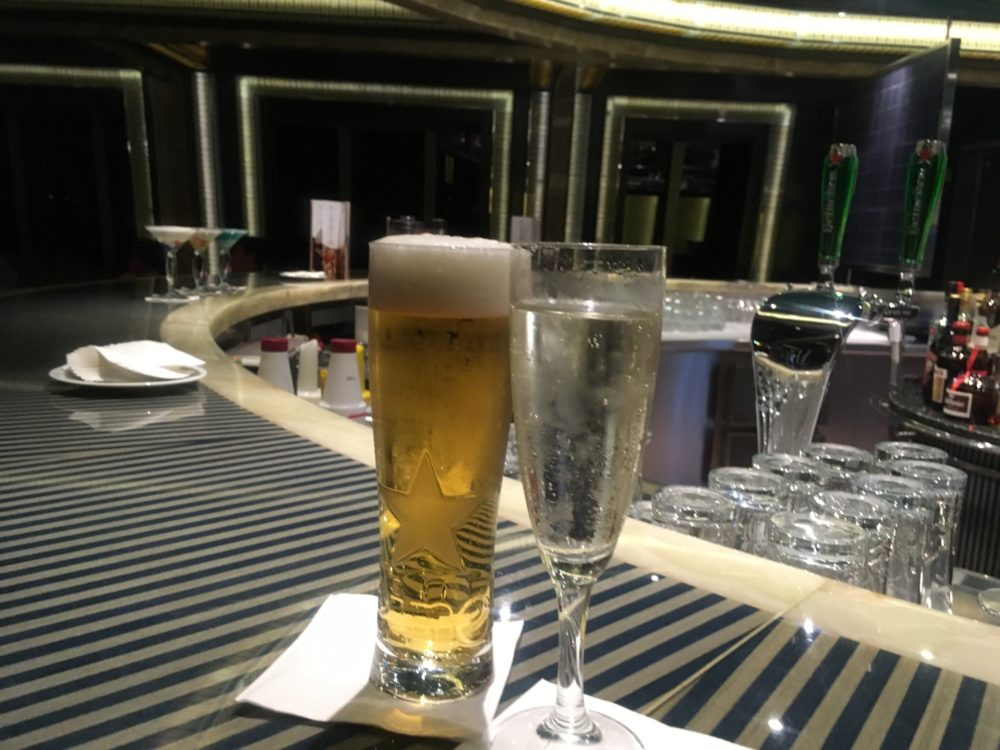 14 Cruise Tips and Tricks Every Cruiser Should Know featured by top US cruise blog, The Common Traveler: image of A pint of beer and a champagne flute at a cruise ship bar.