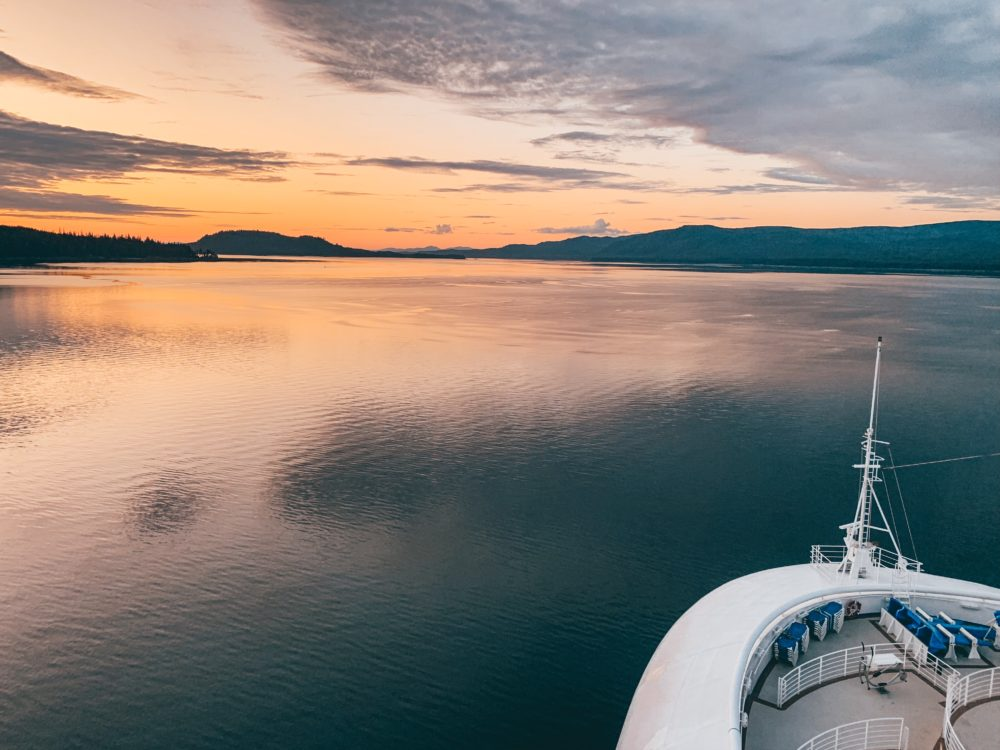 14 Cruise Tips and Tricks Every Cruiser Should Know featured by top US cruise blog, The Common Traveler: image of front of cruise ship with sunsetting over open waters