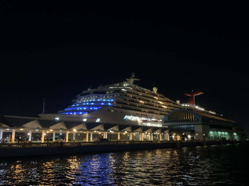 Top 11 Tips for a Smooth Disembarkation Day featured by top US travel blog, The Common Traveler: image of Carnival Conquest at night