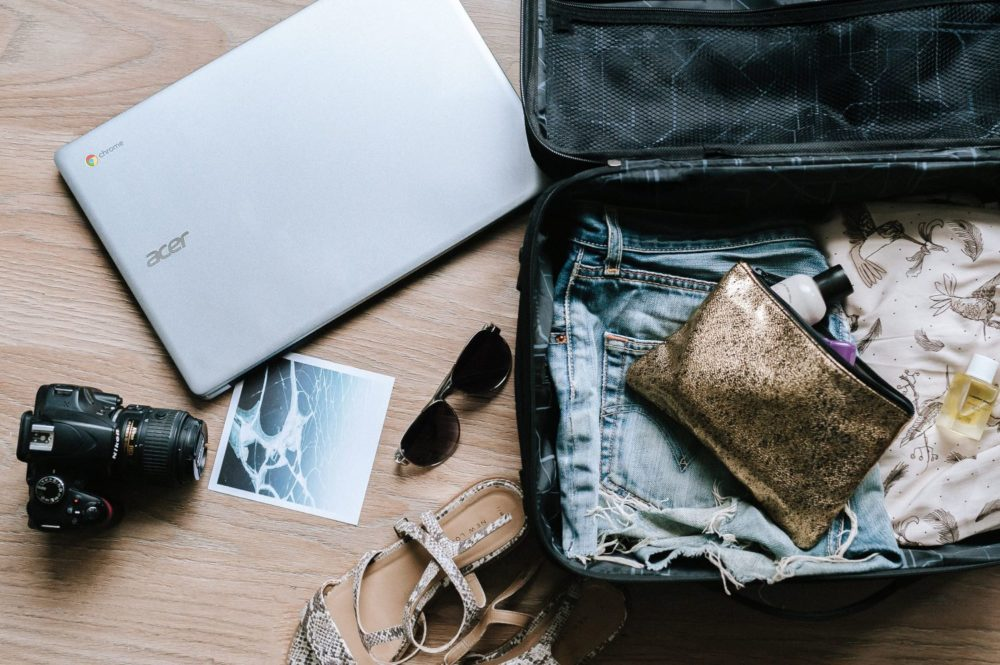 Top 11 Tips for a Smooth Disembarkation Day featured by top US travel blog, The Common Traveler: image of open suitcase with laptop, sunglasses and other items being packed