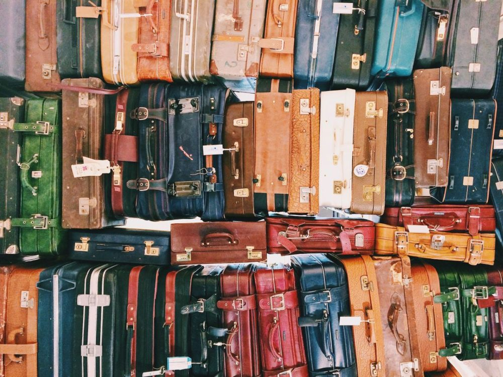 Top 11 Tips for a Smooth Disembarkation Day featured by top US travel blog, The Common Traveler: image of many suitcases stacked together