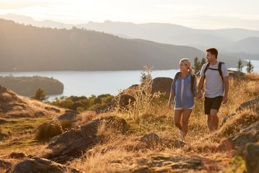 Best Honeymoon destinations in 2020 featured by top travel blog, The Common Traveler: image of  couple walking on hill with lake in background