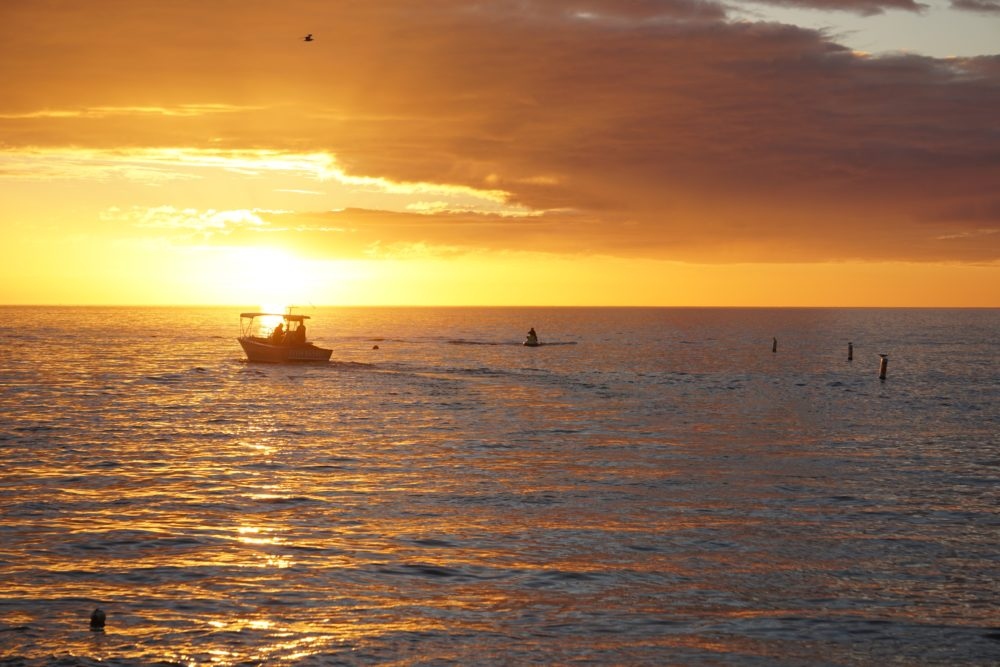Top 5 best places to watch the sunset in SW Florida, featured by top US travel blog, The Common Traveler: image of boat with SWFL sunset