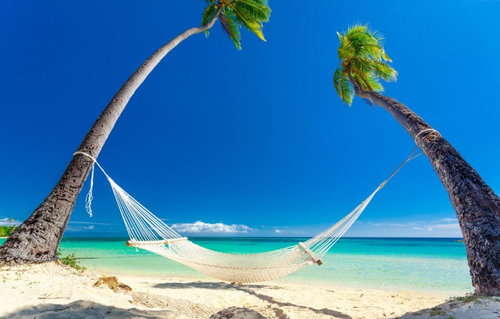 Best Honeymoon destinations in 2020 featured by top travel blog, The Common Traveler: image of  hammock on palm trees on beach in Fiji