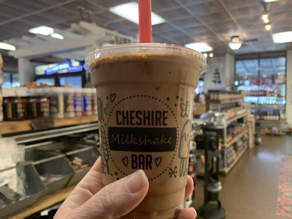 Best Thing to do in Goldsboro - drink a delicious milkshake from Heritage Farms General Store - image of chocolate caramel milkshake in front of store shelves