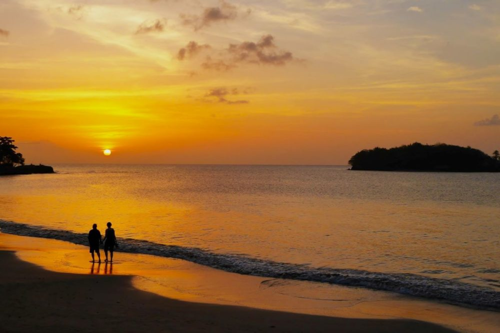 Best Honeymoon destinations in 2020 featured by top travel blog, The Common Traveler: image of  couple walking on beach at sunset