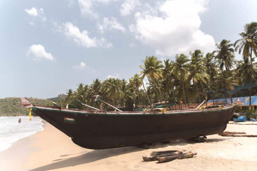 One month India itinerary featured by top travel blog, The Common Traveler. boat on beach in Goa
