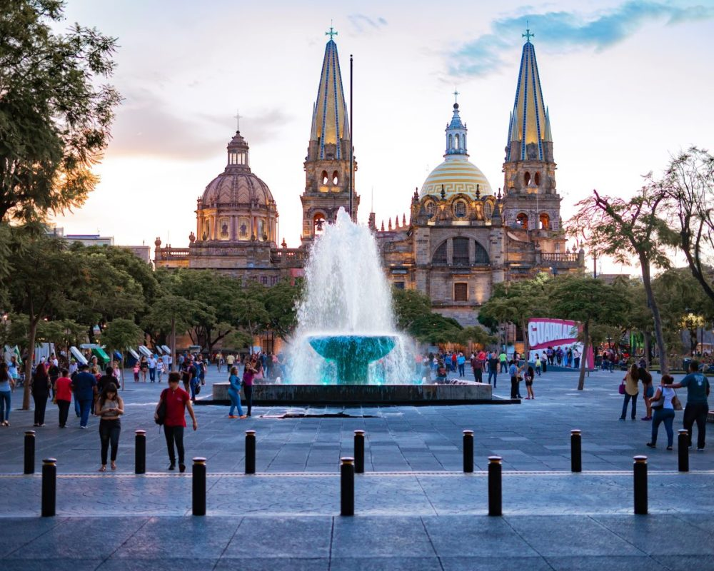 16 BEST PLACES TO VISIT IN MEXICO featured by top travel blog, The Common Traveler: image of plaza in Guadalajara with water front and people in front and large church in background