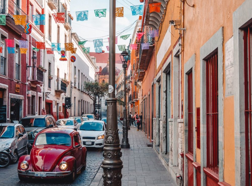 16 BEST PLACES TO VISIT IN MEXICO featured by top travel blog, The Common Traveler: image of street with buildings and cars and colorful flags in Guanajuato as best places to go in Mexico