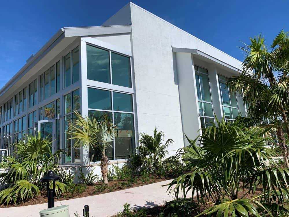WHAT TO DO IN SANIBEL ISLAND OTHER THAN BEACHES featured by top US travel blog, The Common Traveler: image of Sanibel's BIG ARTS building - white marble with glass among palm trees