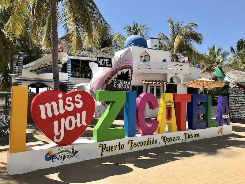 16 BEST PLACES TO VISIT IN MEXICO featured by top travel blog, The Common Traveler: image of I miss you Zicatela sign in front of hotel in Puerto Escondido, Mexico