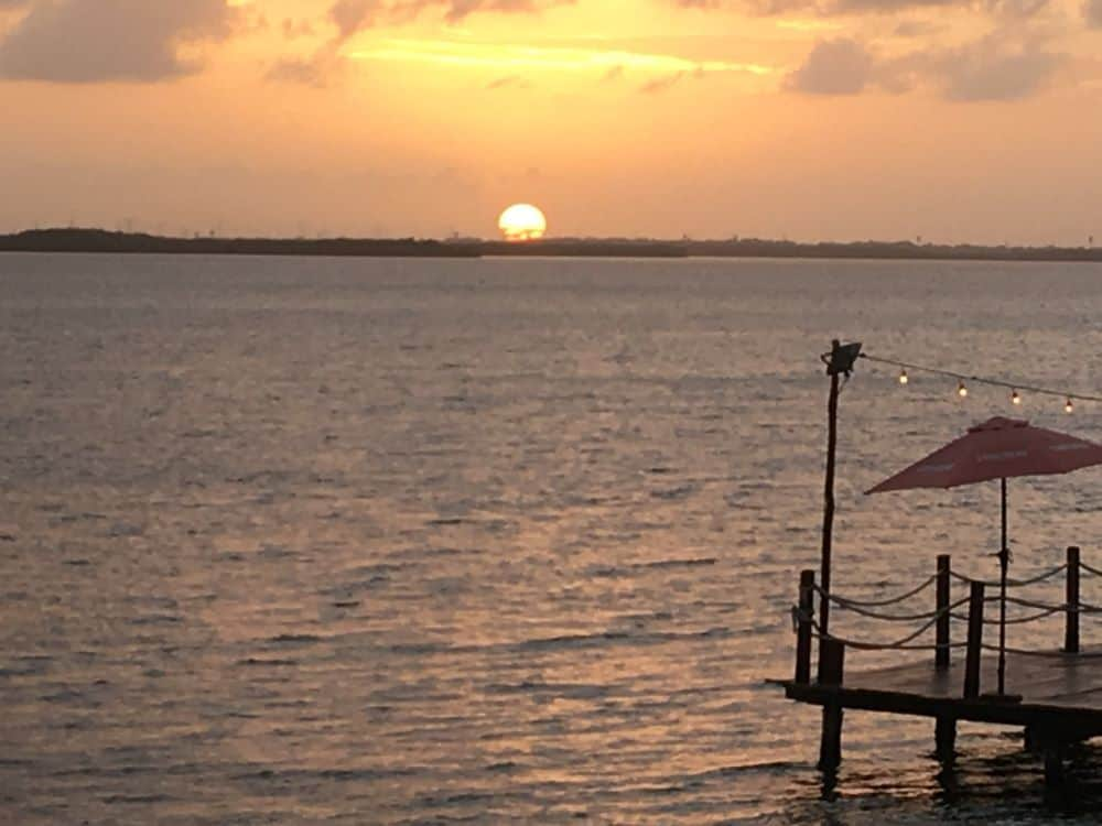 16 BEST PLACES TO VISIT IN MEXICO featured by top travel blog, The Common Traveler: image of sunset over dock in Cancun, Mexico