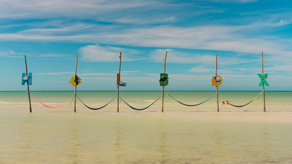 "16 BEST PLACES TO VISIT IN MEXICO featured by top travel blog, The Common Traveler: image of sticks with letters and hammocks on shore spelling ""Holbox"" in best places to visit in Mexico"