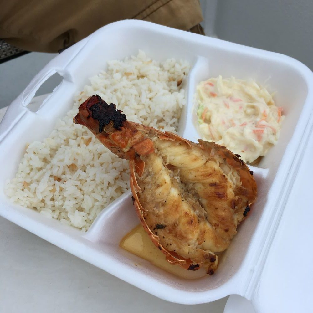The Best Restaurants in San Pedro Belize featured by top travel blog, The Common Traveler; photo of lobster tail with rice and coleslaw at Delicia's Deli