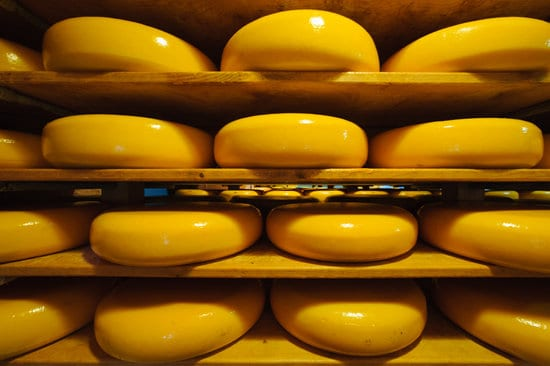 TOP 10 BEST ARUBA SOUVENIRS TO BUY featured by top travel blog, The Common Traveler: image of Dutch cheese ripening on the shelves at a dairy farm.