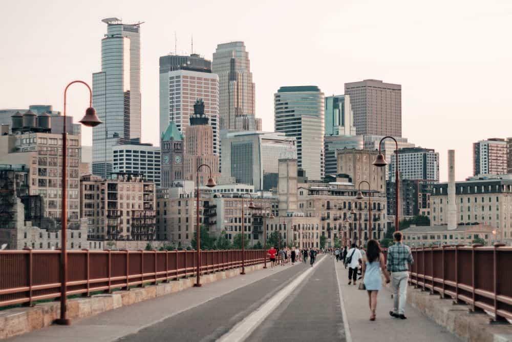 TOP 20 BEST WEEKEND GETAWAYS IN THE US featured by top US travel blog, The Common Traveler: image of  people walking on bridge with Minneapolis, Minnesota skyline in background