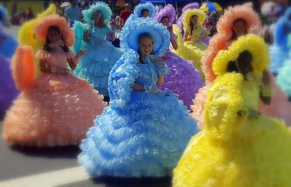 TOP 20 BEST WEEKEND GETAWAYS IN THE US featured by top US travel blog, The Common Traveler: image of  ladies in pastel Southern belle dresses and umbrellas in parade in Mobile, Alabama