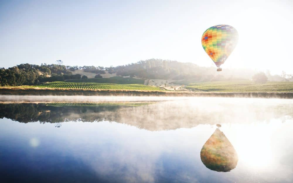 TOP 20 BEST WEEKEND GETAWAYS IN THE US featured by top US travel blog, The Common Traveler: image of  hot air balloon reflected in lake in Napa Valley, California
