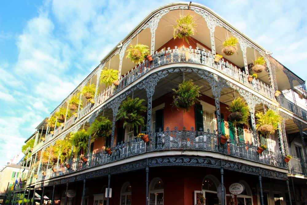 TOP 20 BEST WEEKEND GETAWAYS IN THE US featured by top US travel blog, The Common Traveler: image of  iron work balconies with ferns and flower pots in New Orleans, Louisiana