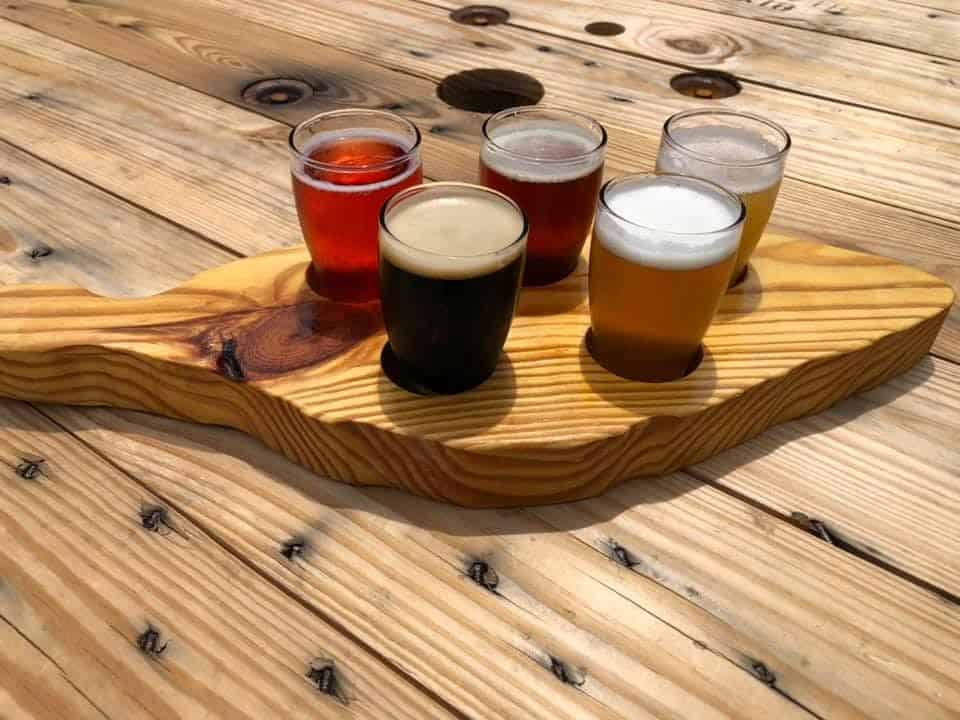 BEST VETERAN OWNED BREWERIES IN NC featured by top NC travel blog, The Common Traveler: flight of beers on wooden board from Tobacco Wood Brewing Co. in Oxford, NC