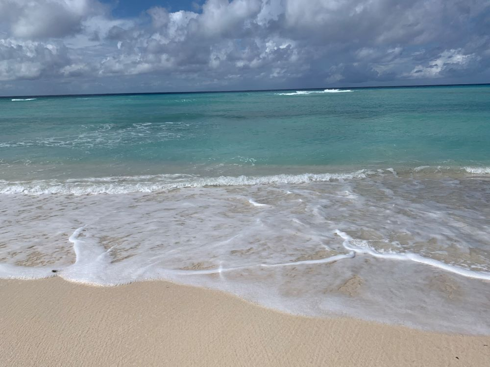 The best things to do in Grand Turk Island on port day featured by top cruise travel blogger, The Common Traveler: sand and waves at Cockburn Town beach in Grand Turk