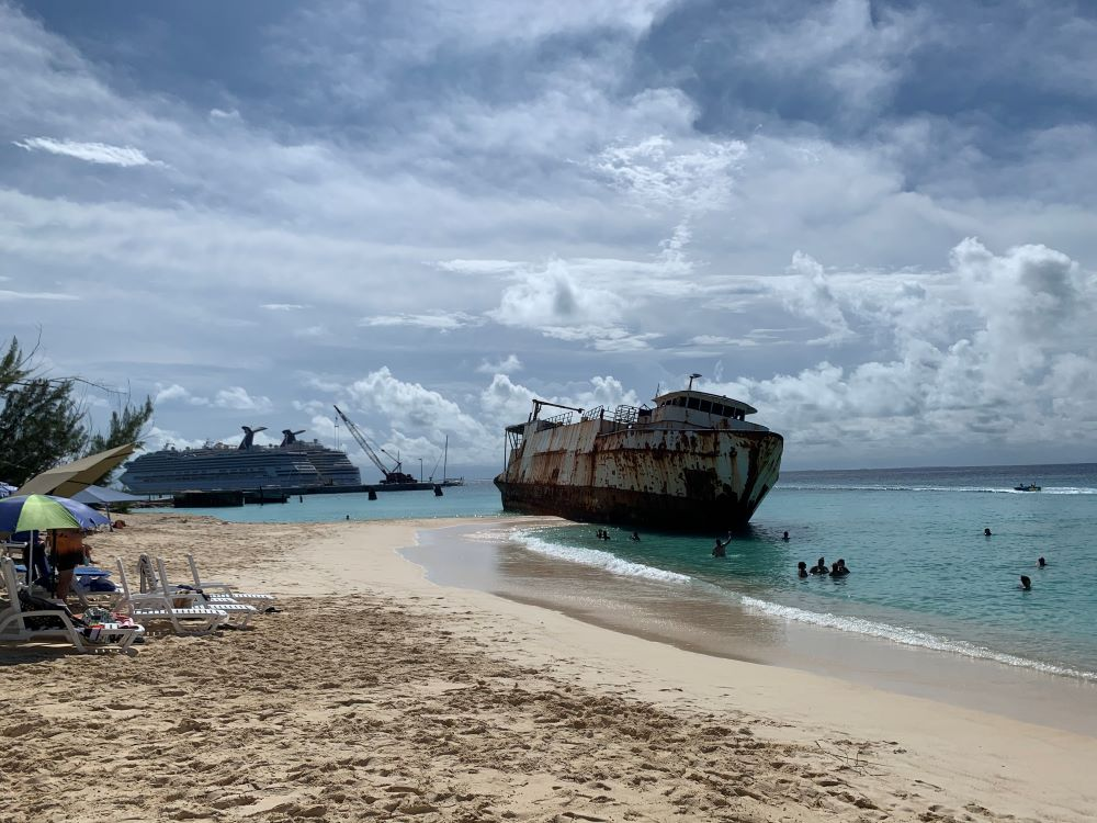 The best things to do in Grand Turk Island on port day featured by top cruise travel blogger, The Common Traveler: beach with moored ship with two Carnival ships in background in Grand Turk