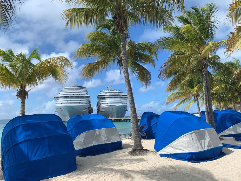The best things to do in Grand Turk Island on port day featured by top cruise travel blogger, The Common Traveler: wind and sun shelters on beach with palm trees with two Carnival cruise ships in Grand Turk
