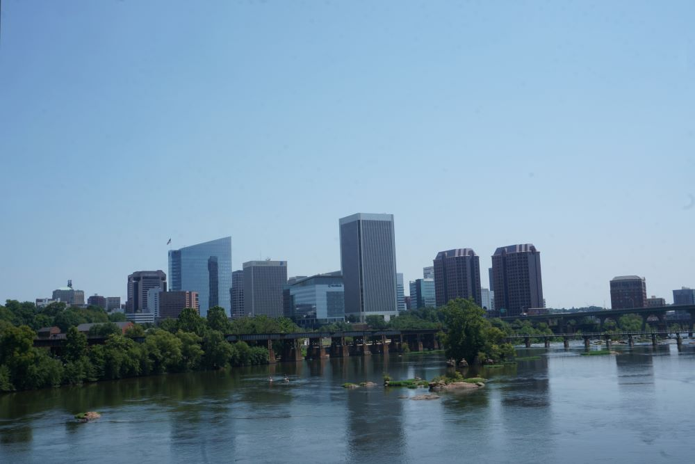 WEEKEND IN RICHMOND VA travel guide featured by top US travel blogger, The Common Traveler. Image of Richmond Skyline during the day with river in the foreground