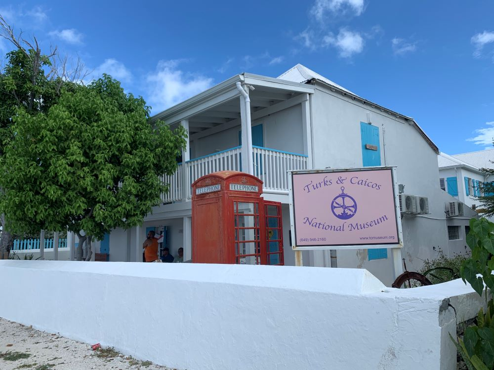 The best things to do in Grand Turk Island on port day featured by top cruise travel blogger, The Common Traveler: white building with red telephone booth - Turks & Caicos National Museum