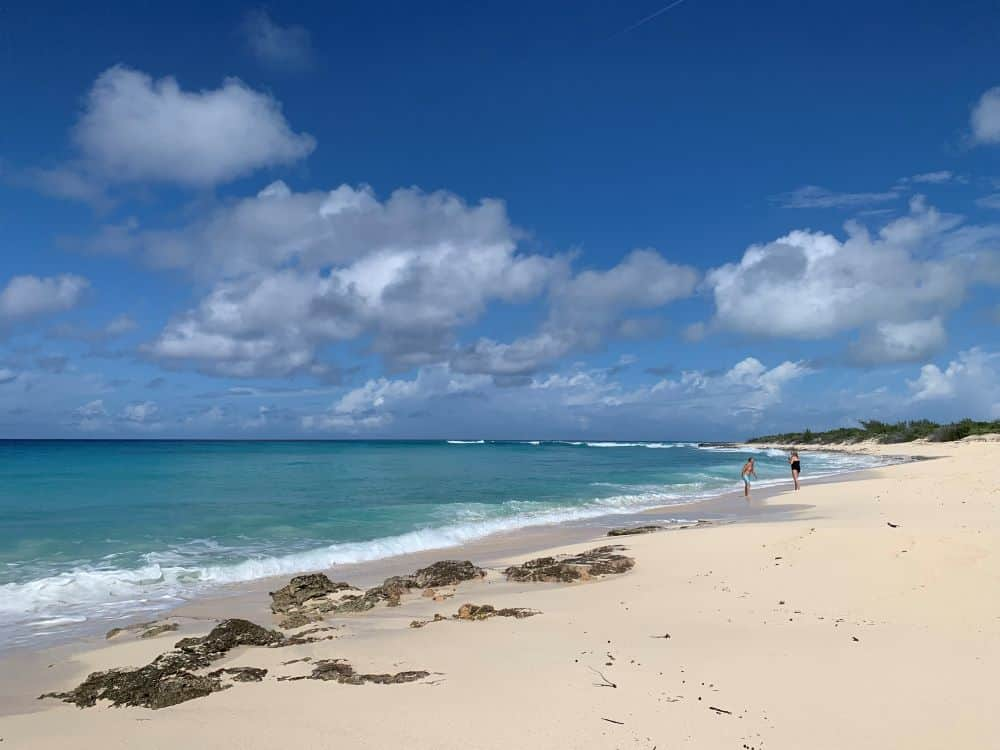 The best things to do in Grand Turk Island on port day featured by top cruise travel blogger, The Common Traveler: couple on English Point Beach in Grand Turk