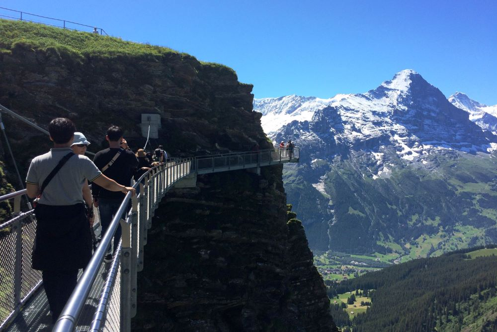 TOP 6 BEST SIGHTS IN SWITZERLAND TO SEE IN 48 HOURS featured by top travel blogger, The Common Traveler: image of metal cliff walk along mountain edge in Alps