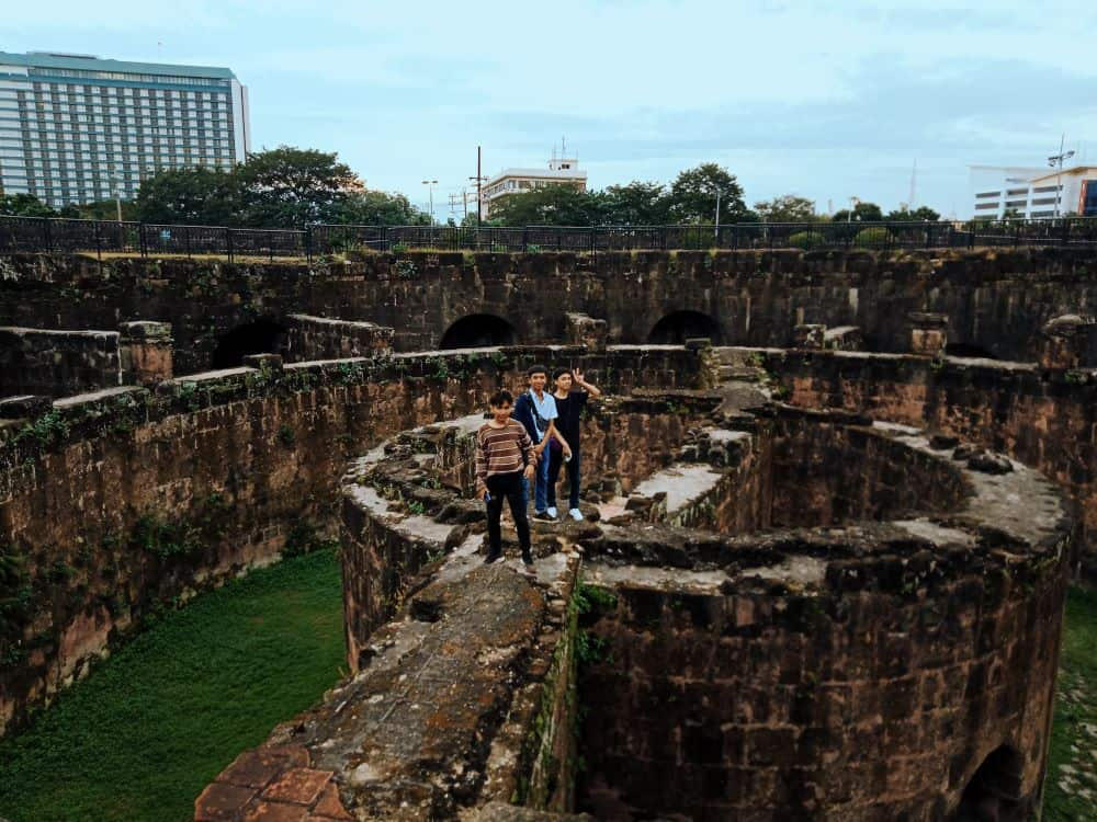 8 BEST THINGS TO DO IN MANILA featured by top travel blogger, The Common Traveler. Image: kids on wall in Intramuros, Manila, Philippines.