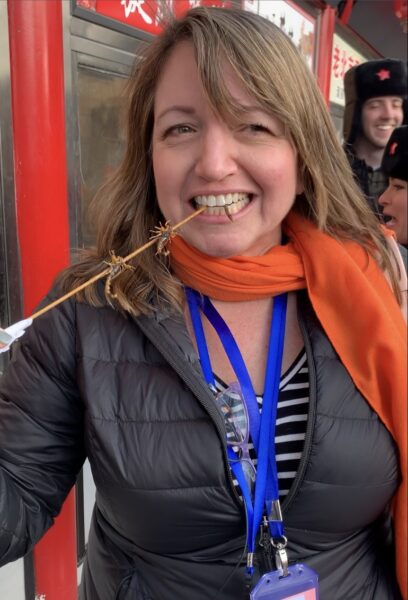 woman eating scorpions on a stick in Beijing, China