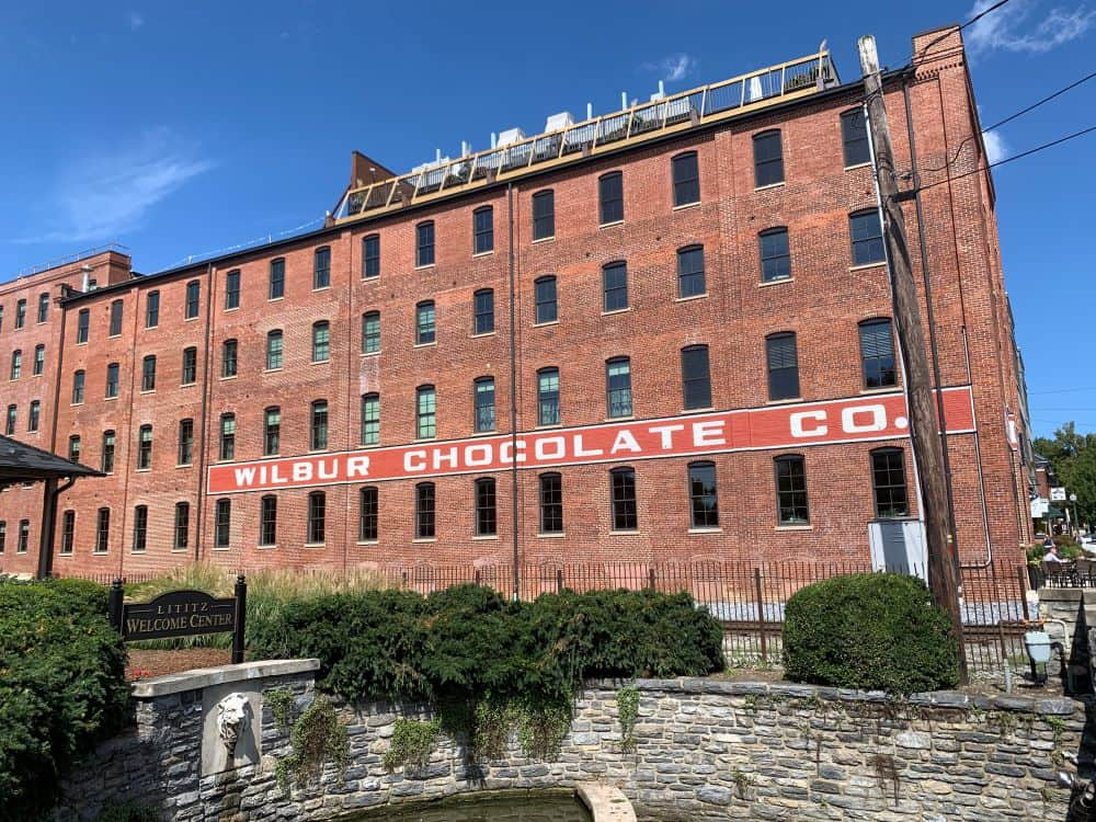 THE BEST THINGS TO DO IN LITITZ PA featured by top US travel blogger, The Common Traveler: image of brick building, former Wilbur Chocolate Co. Lititz PA