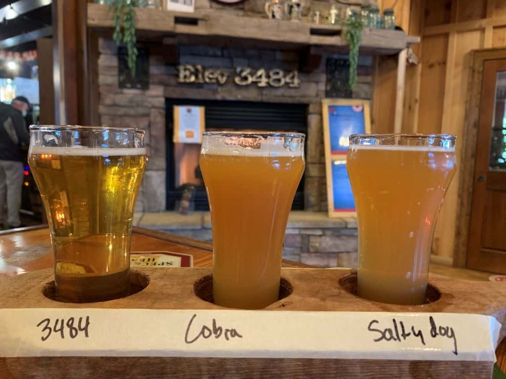 flight of 3 beers in front of fireplace at Whiteside Brewing, Cashiers, NC