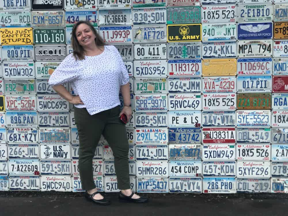 woman in front of wall license plates on building in Sylva, NC